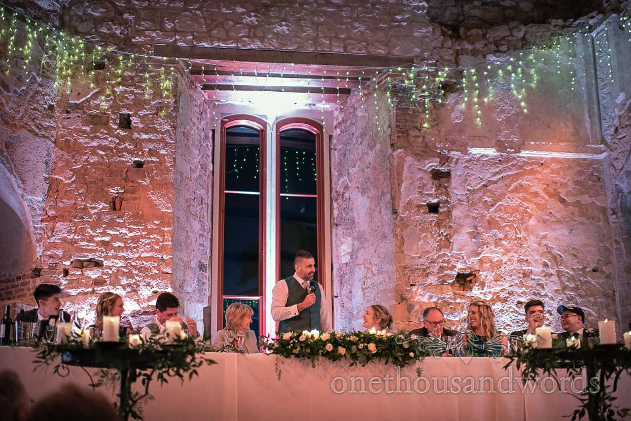 Groom delivers speech from top table at Lulworth Castle wedding reception