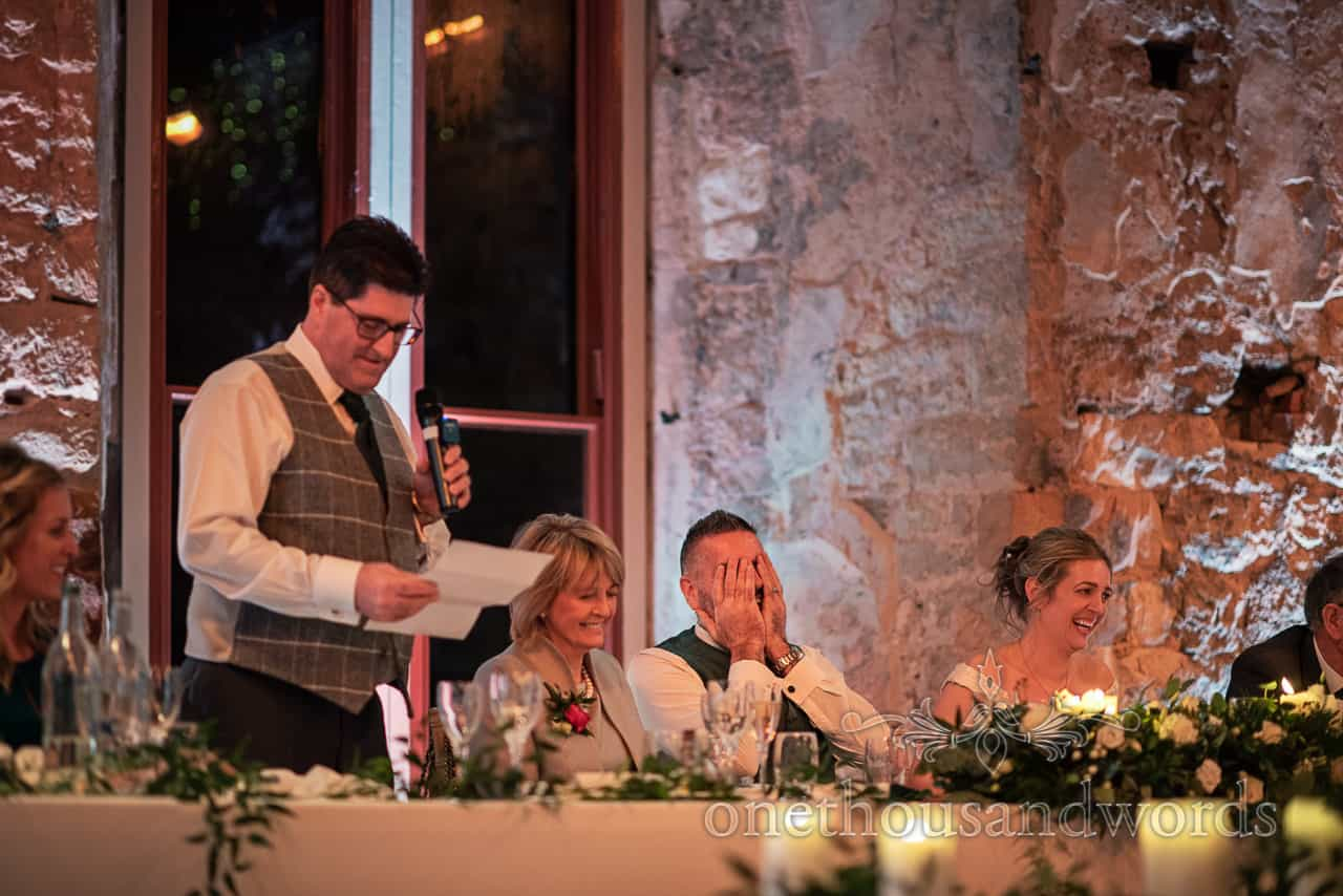 Groom hold head in hands during best man speech at Lulworth Estate wedding photographs