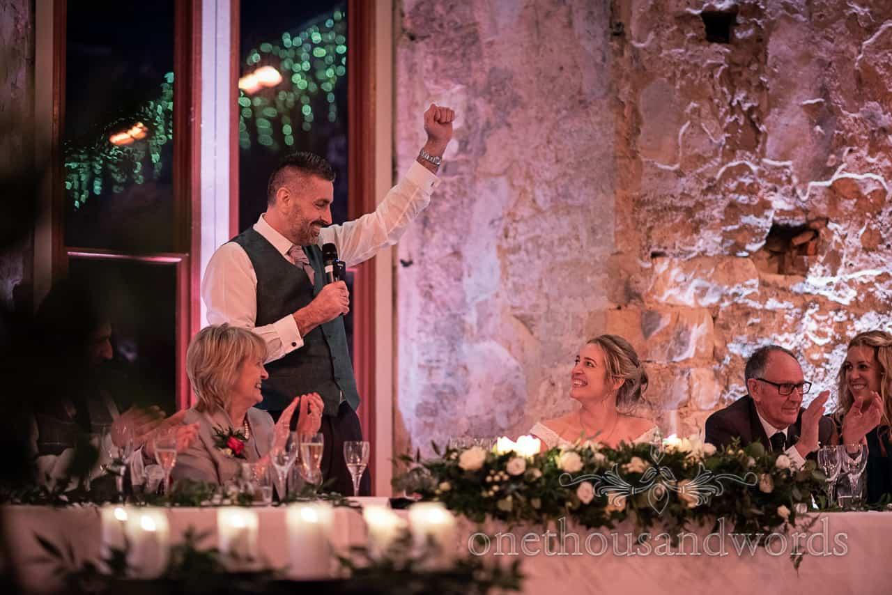 Groom punches the air during speech at Lulworth Estate wedding