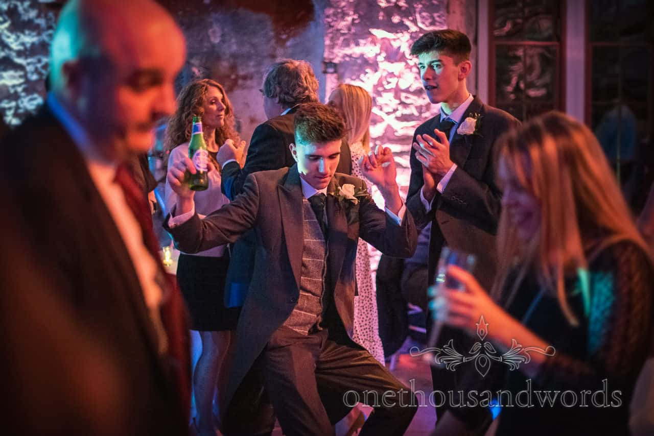 Groomsman throwing shapes on dance floor at Lulworth Estate wedding reception