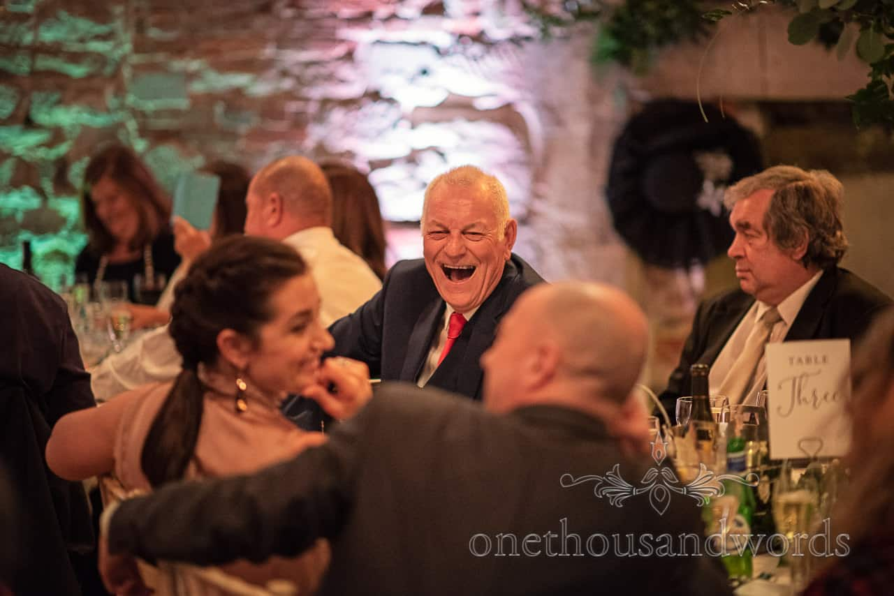 Laughing guest during speeches at Lulworth Castle wedding