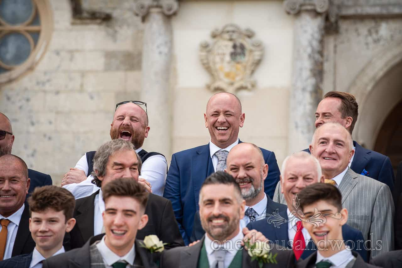 Laughing guests during group photos at Lulworth Castle wedding