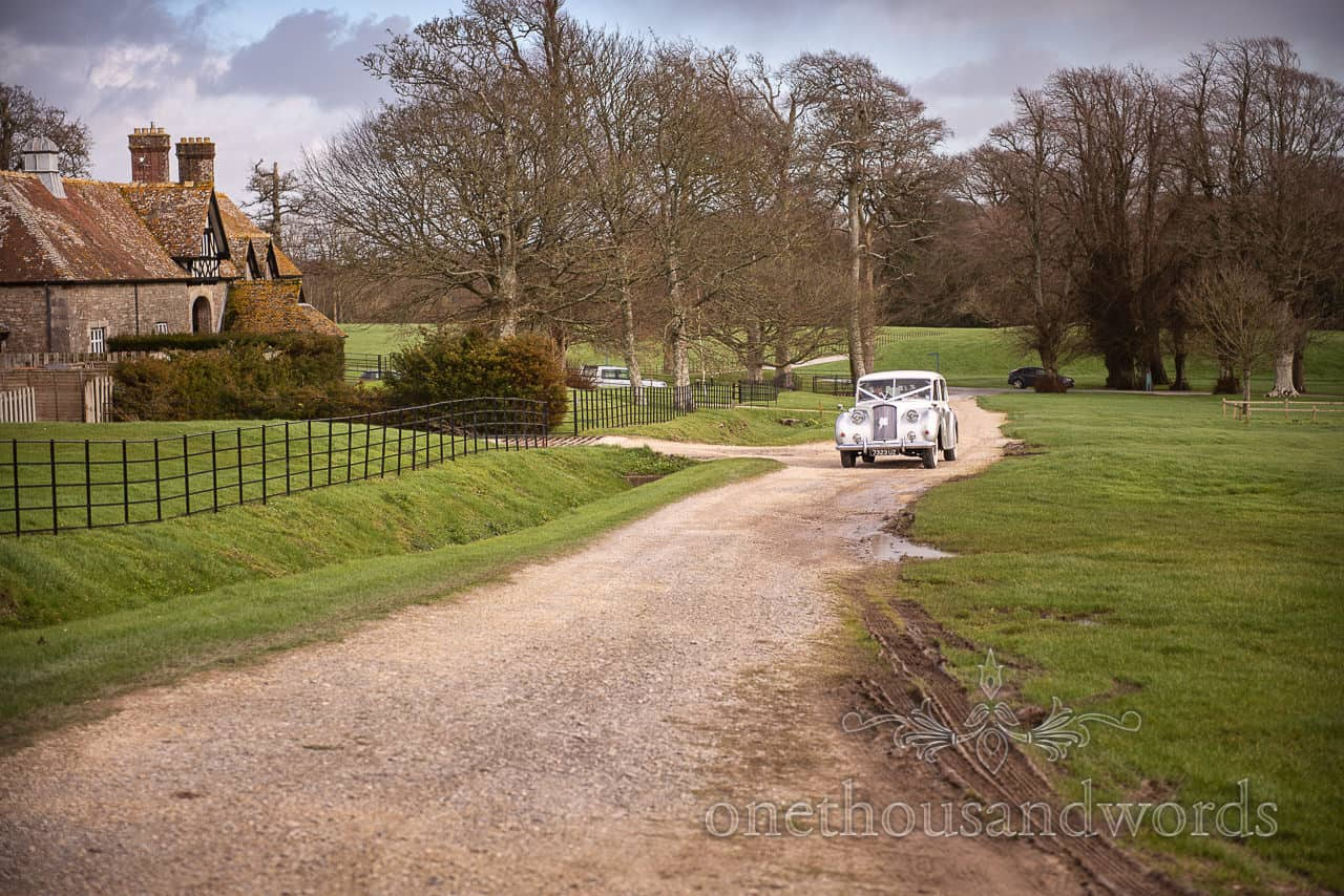 Classic car approaches the church carrying bride at Lulworth Estate wedding photographs