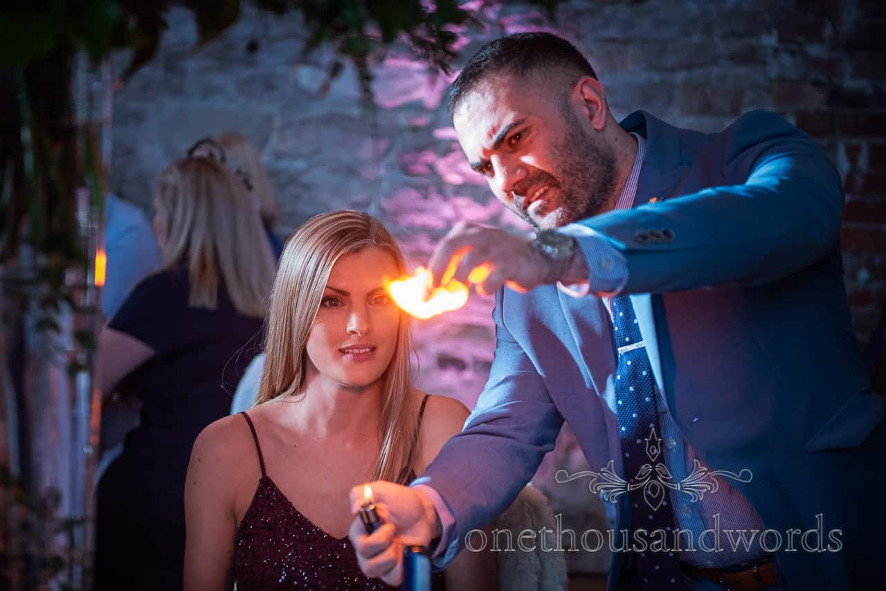 magician watched by guest as he performs trick with flame