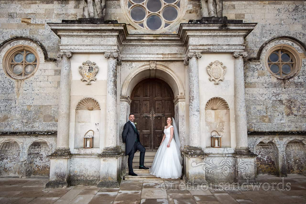 Lulworth Estate wedding photographs of newlyweds outside front door of castle