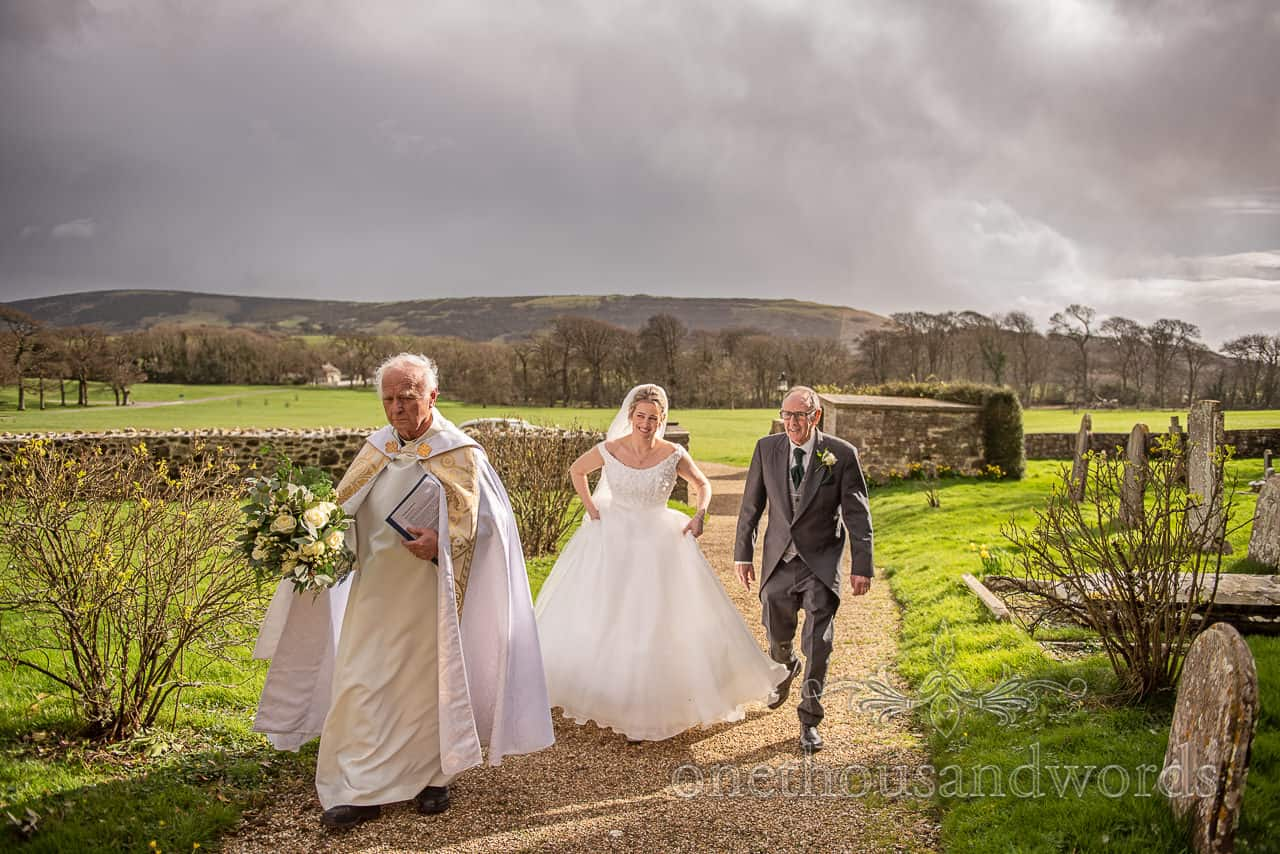 Lulworth Estate Wedding photographs of vicar,bride and father outside church