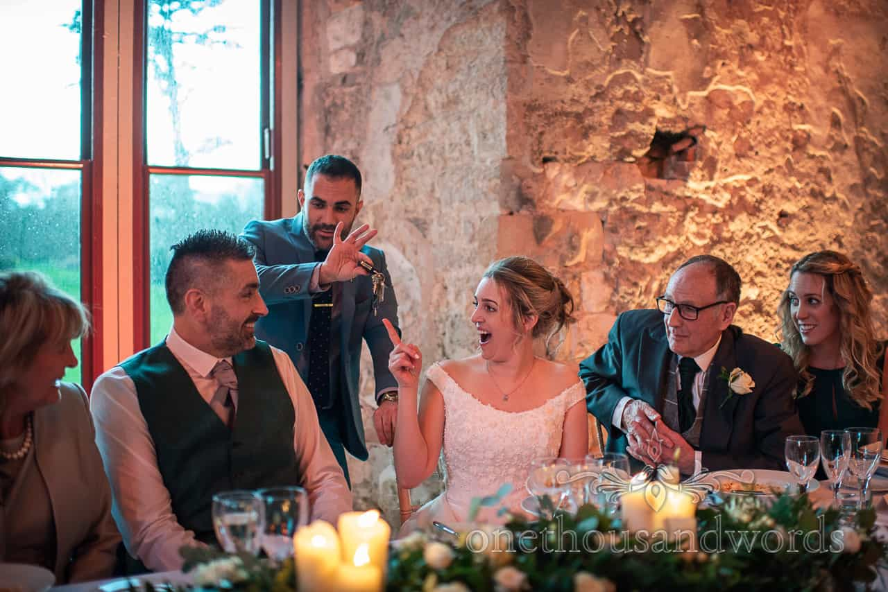 Magician entertains newlyweds at top table from Lulworth Estate wedding reception