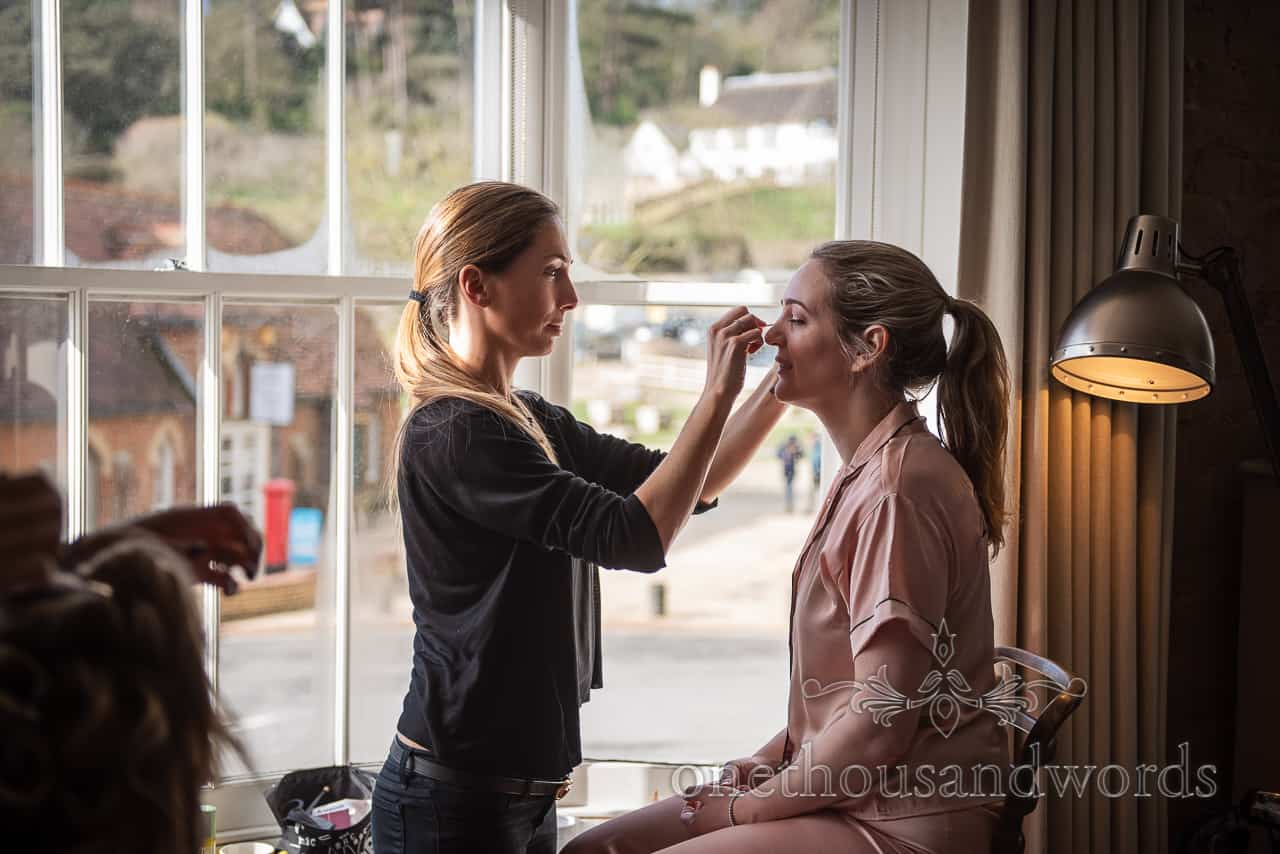 Make up artist and bride in window on wedding morning in Lulworth Hotel