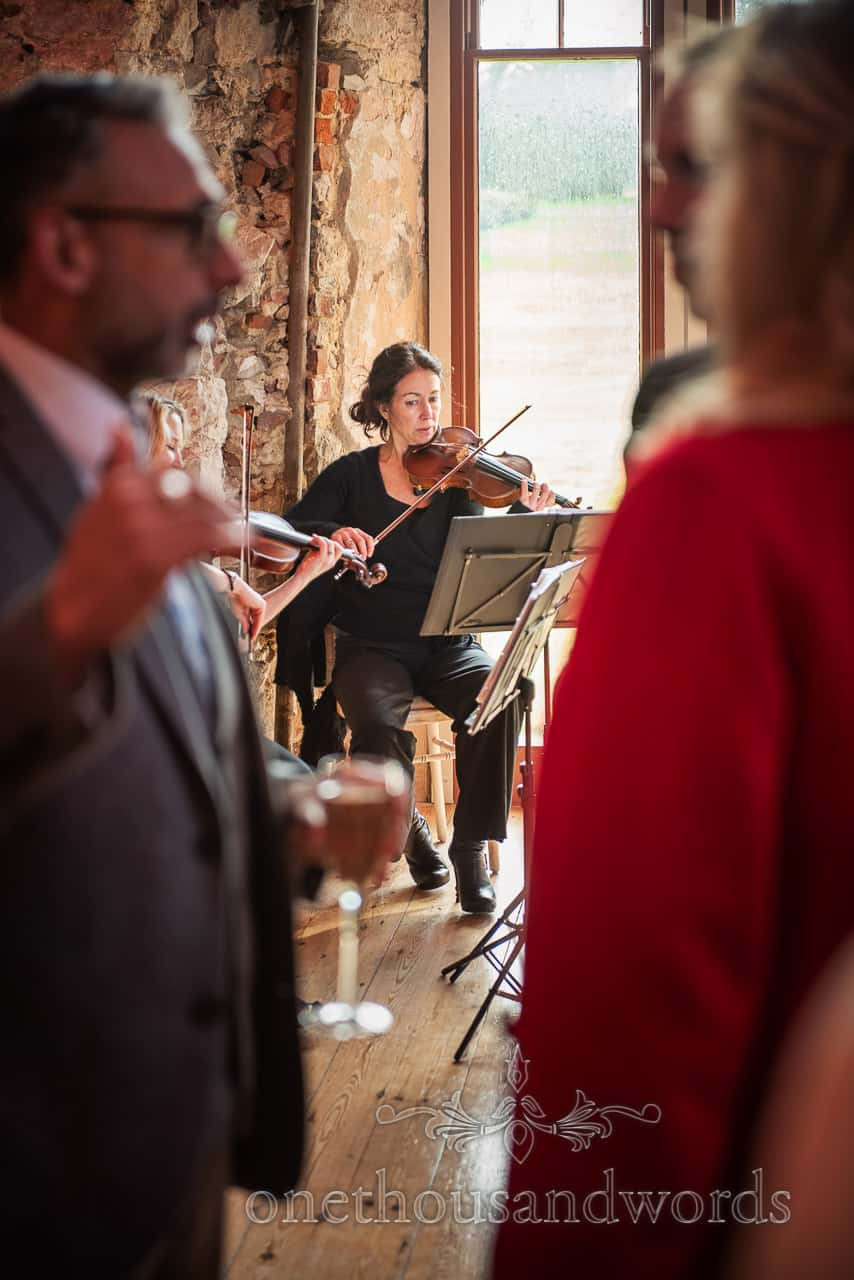 Member of string quartet plays violin to guests during drinks reception