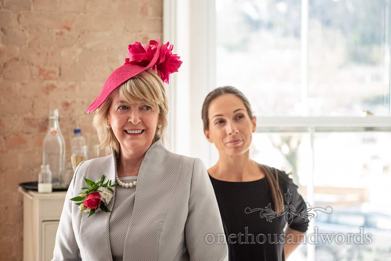 Smiling mother of bride with matching corsage and pink wedding hat
