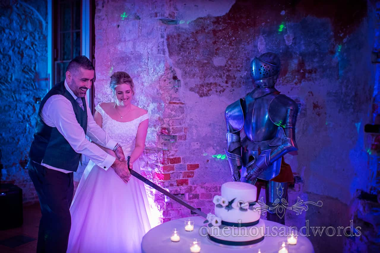 Newlyweds cut the cake with sword next to suit of armour under blue lights
