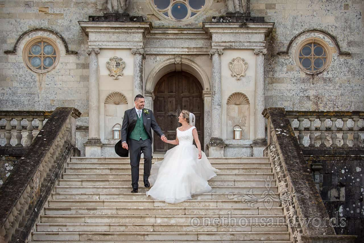 Newlyweds descend stairs at Lulworth Castle wedding photographs
