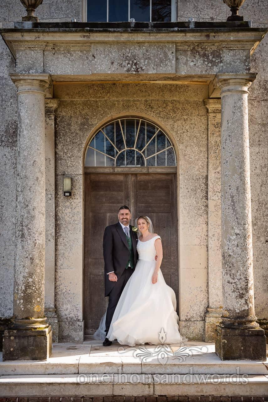 Newlyweds in doorway of Lulworth Estate Catholic chapel