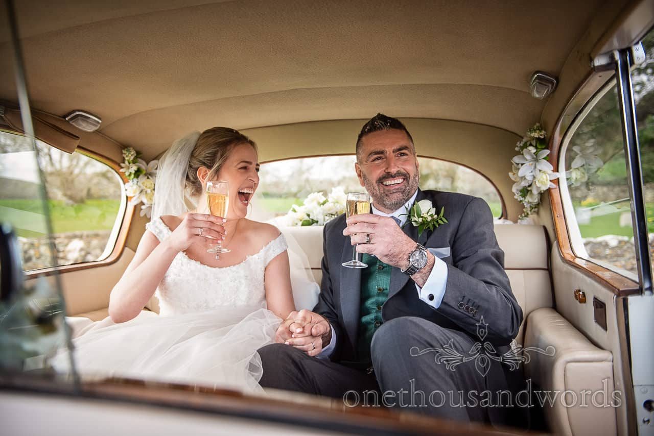 Newlyweds drink bubbles in car at Lulworth weddings