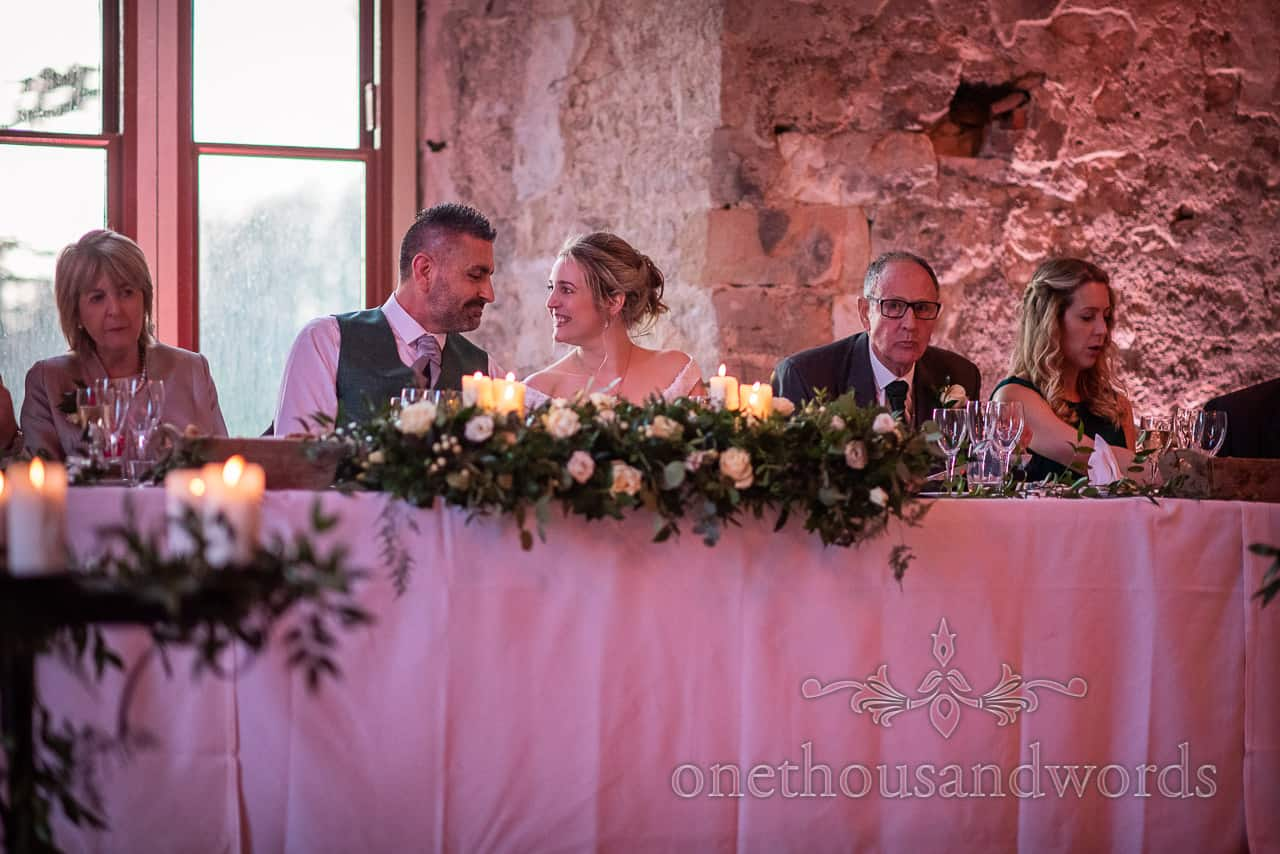 Bride and groom share a moment together at top table