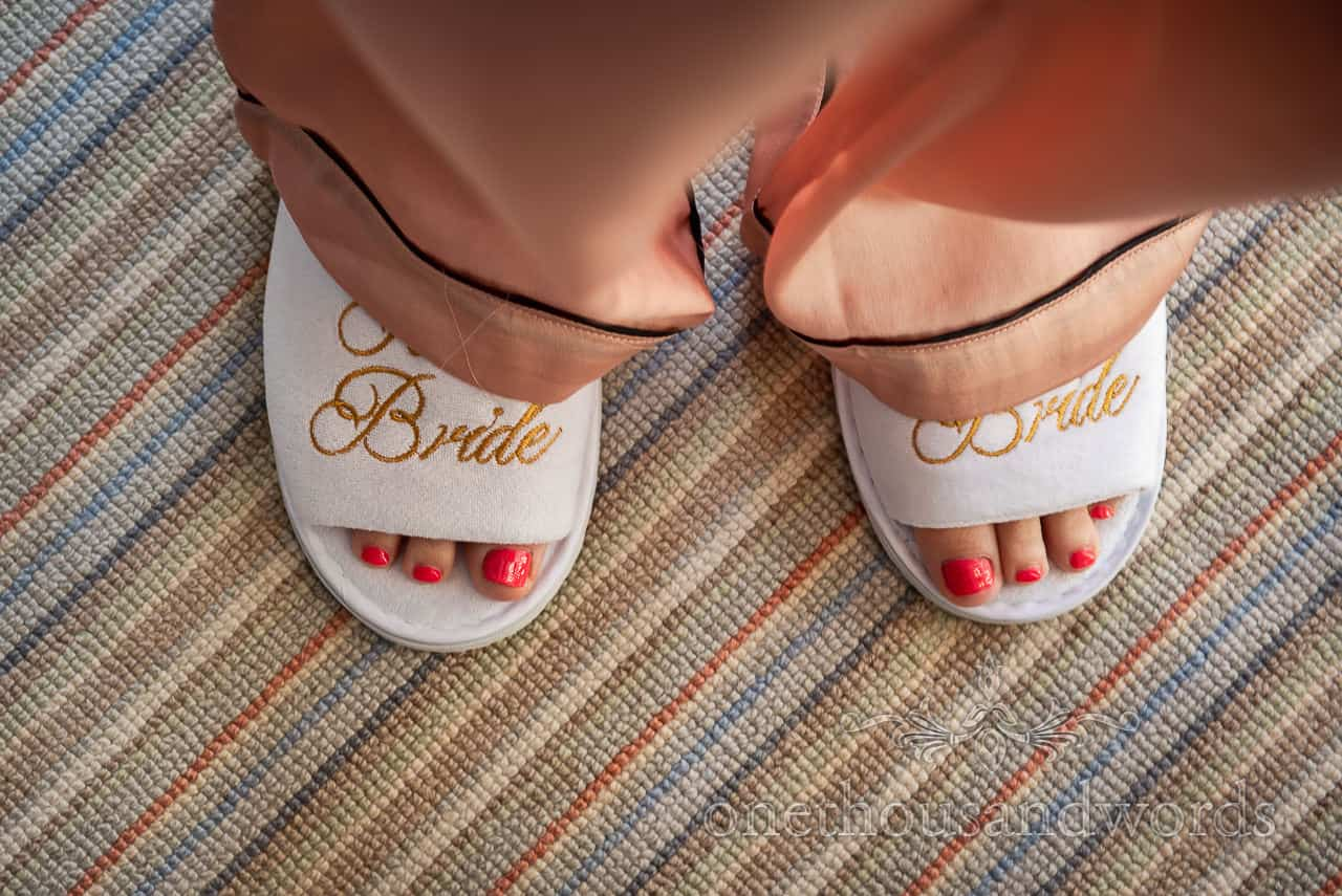 Red painted toes in gold script bride slippers