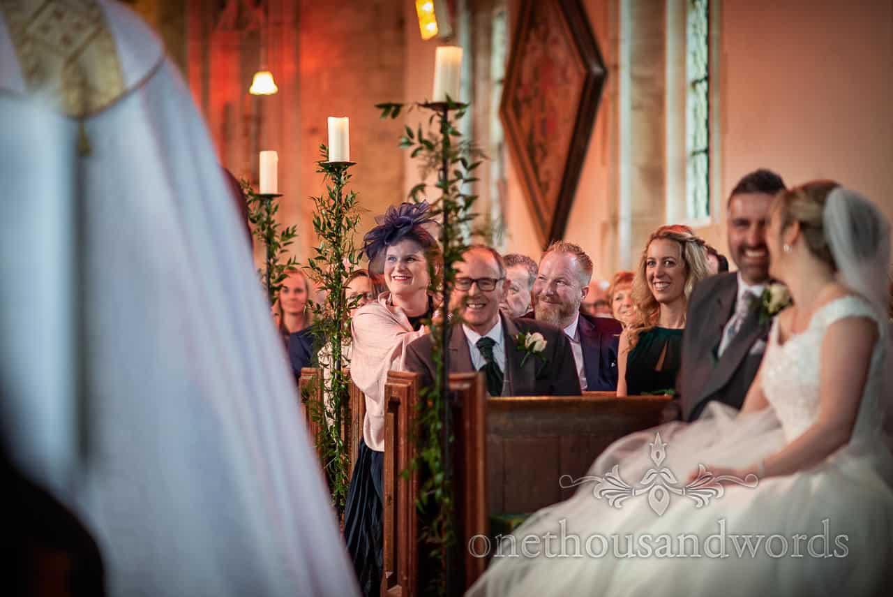 Smiling guests during ceremony at Lulworth Estate church wedding photographs