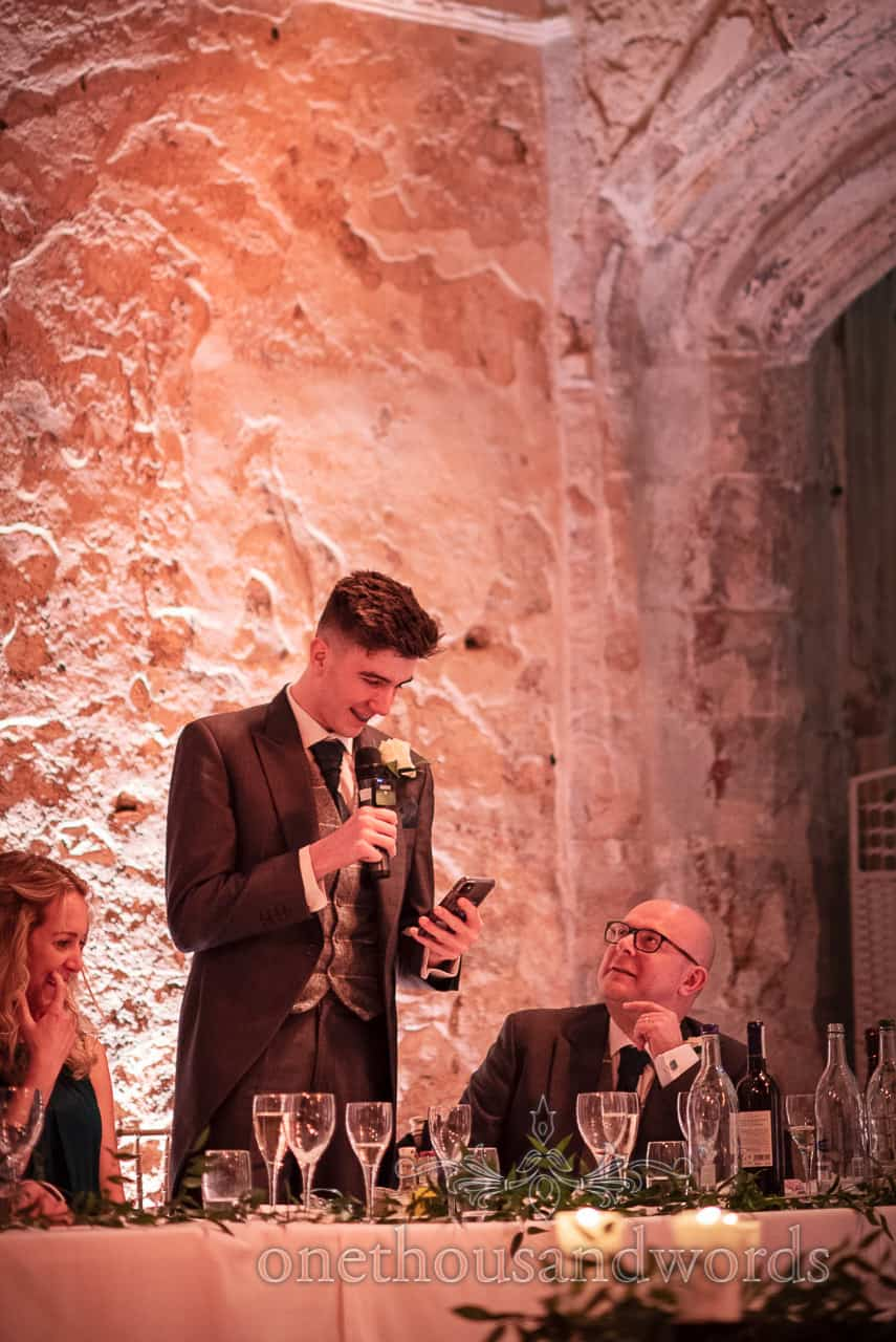 Son of groom delivers speech from smartphone at Lulworth Estate wedding photographs