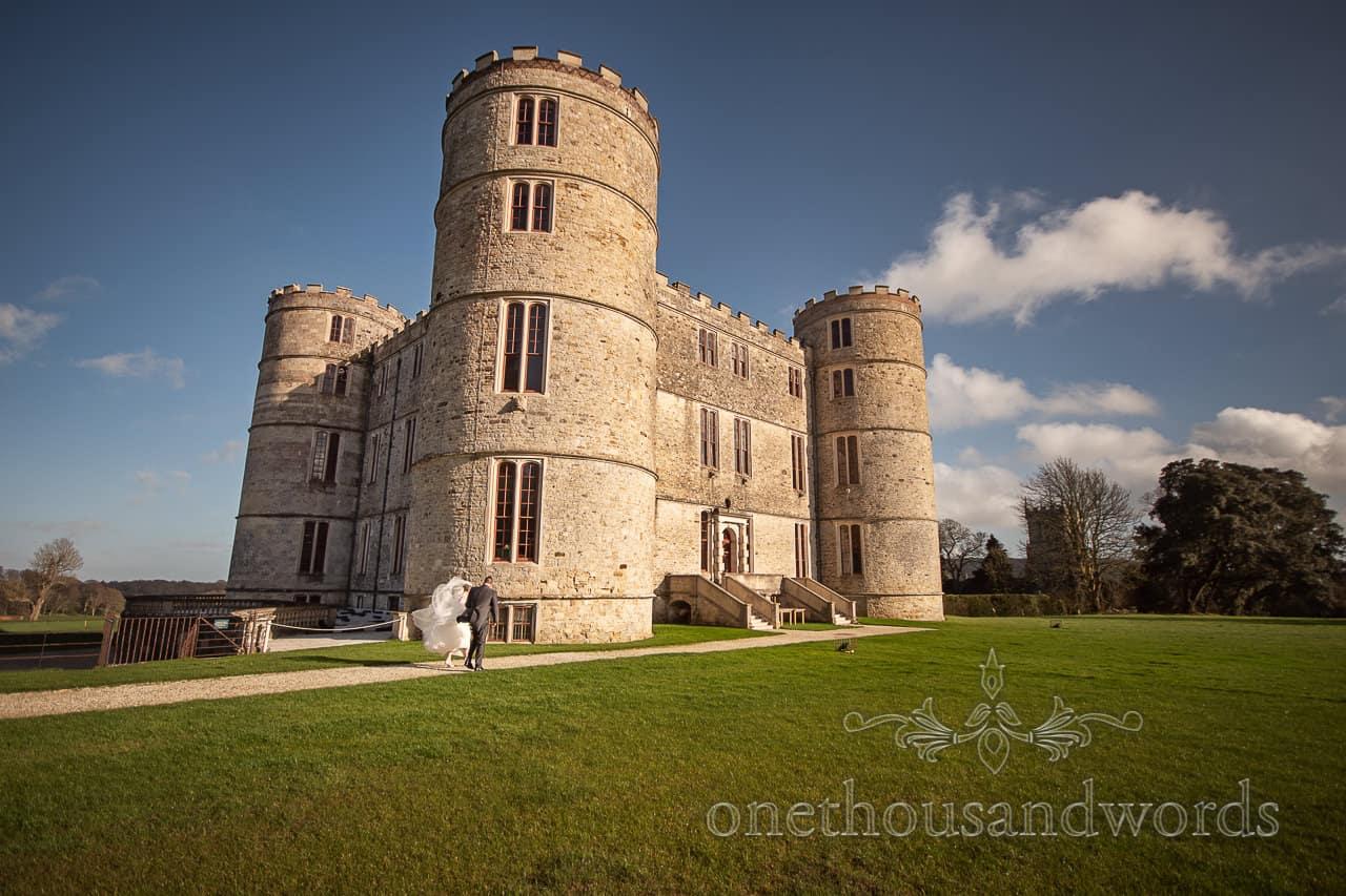 Windswept newlyweds outside Lulworth Castle in sunshine