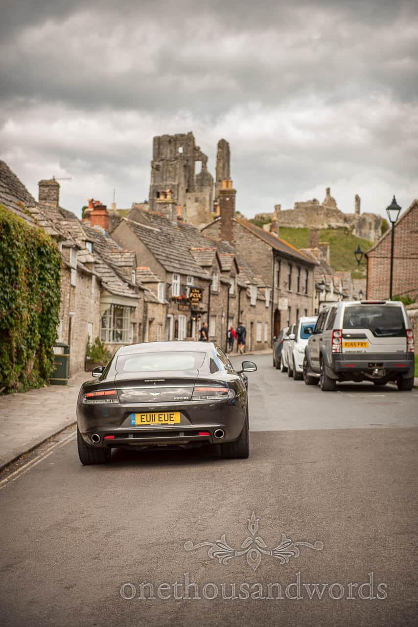 Aston Martin wedding car drives through Corfe Castle village in Dorset