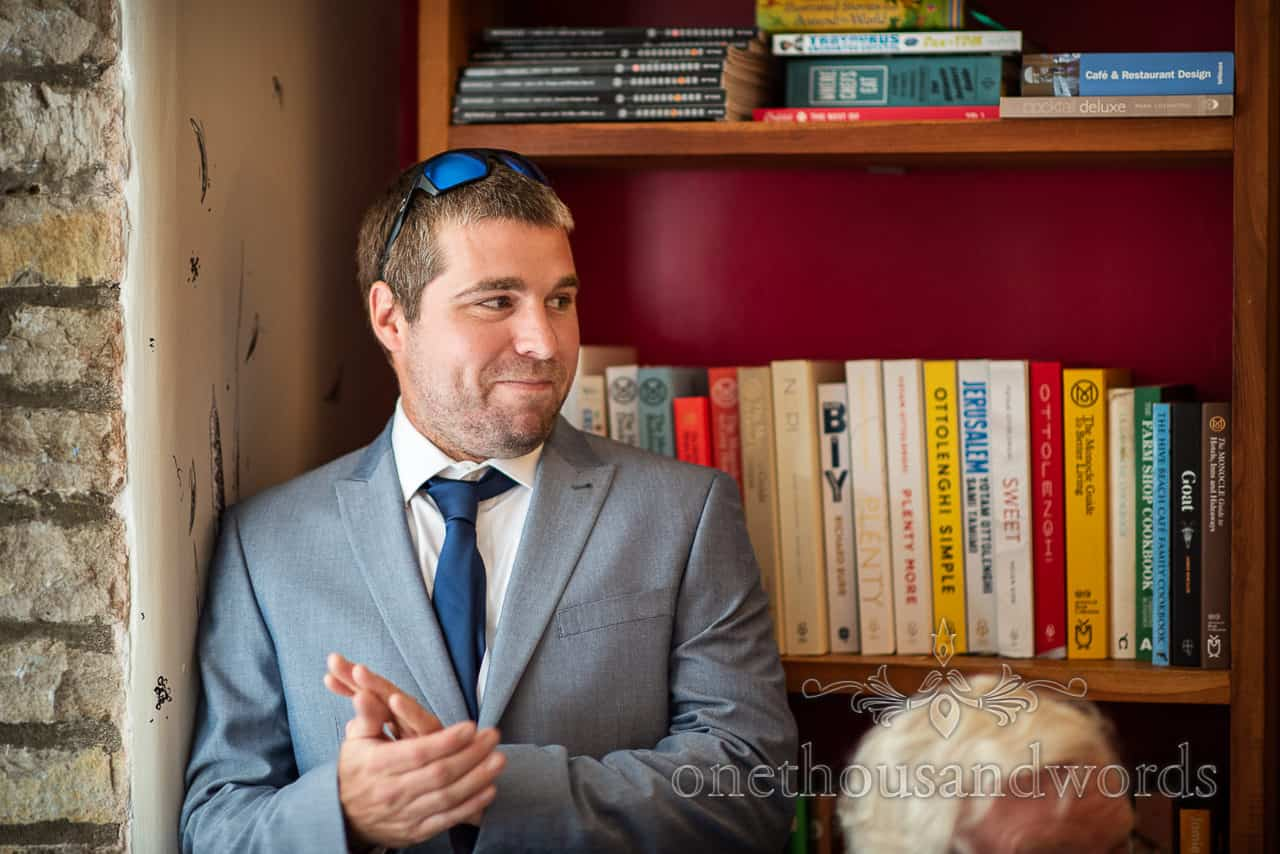 Best man in blue suit and tie with sunglasses claps wedding speeches stood next to bookshelves