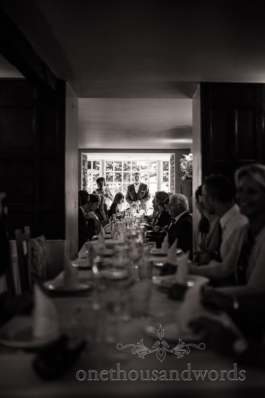 black and white wedding photograph of wedding breakfast table with bride and groom standing at the end