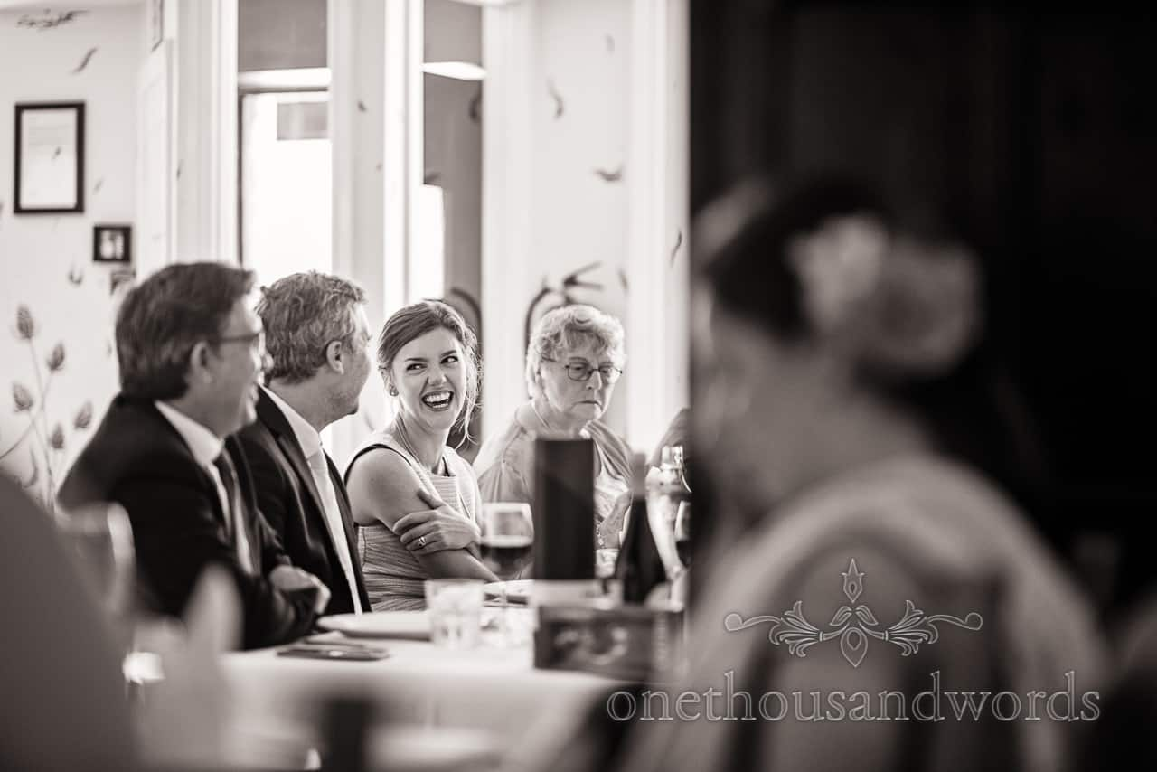 Black and white photograph of female wedding guest laughing during wedding breakfast