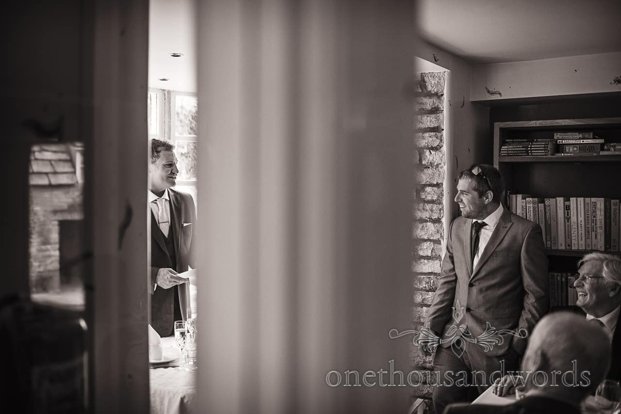 black and white documentary wedding photograph of best man reacting to groom's wedding speech
