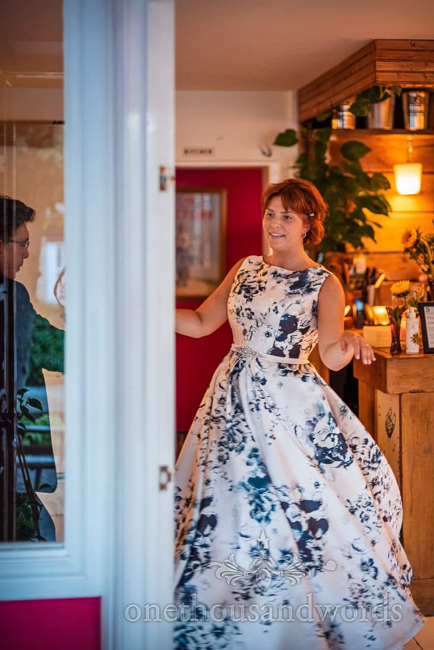 Bride in floral dress dancing photograph taken through doorway