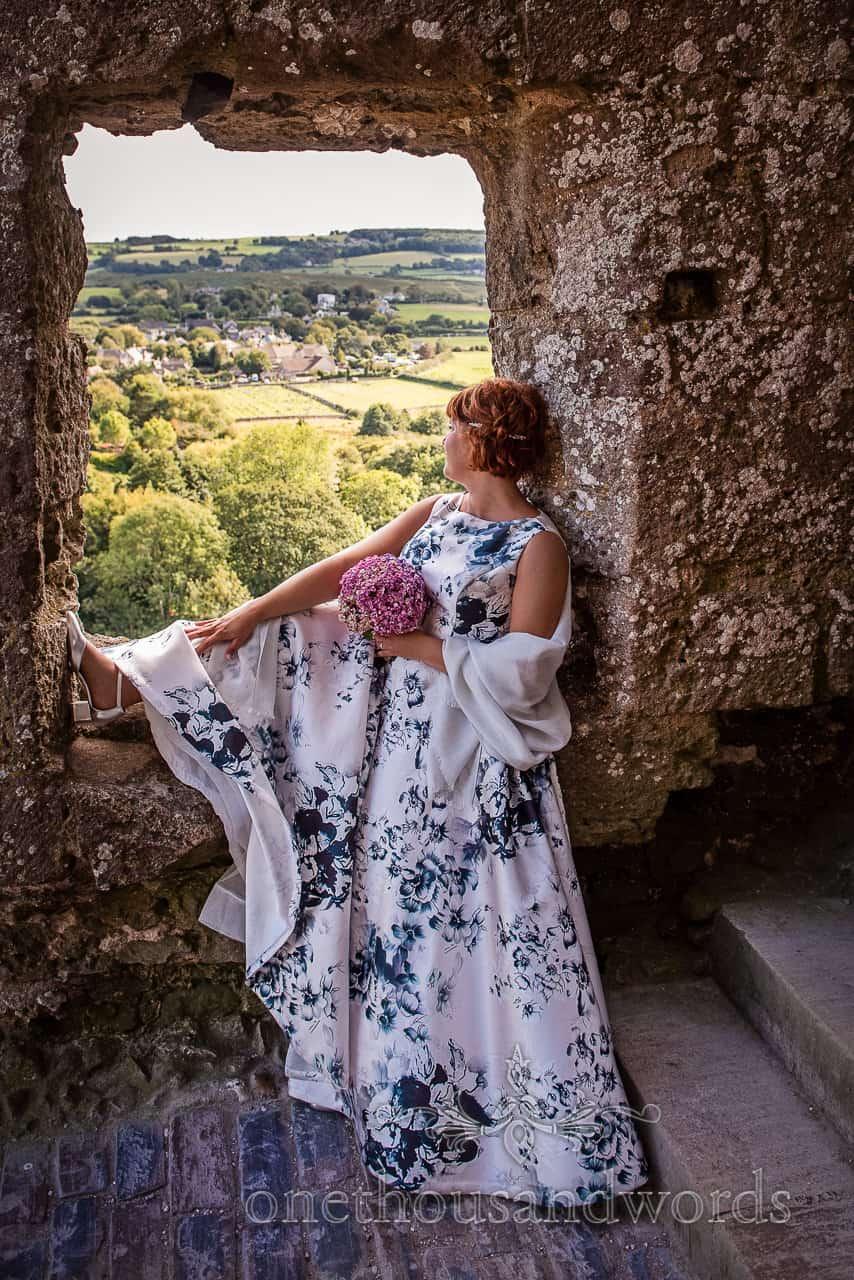 Bride wears blue flower print wedding dress sat in Corfe Castle ruins window looking at Dorset countryside