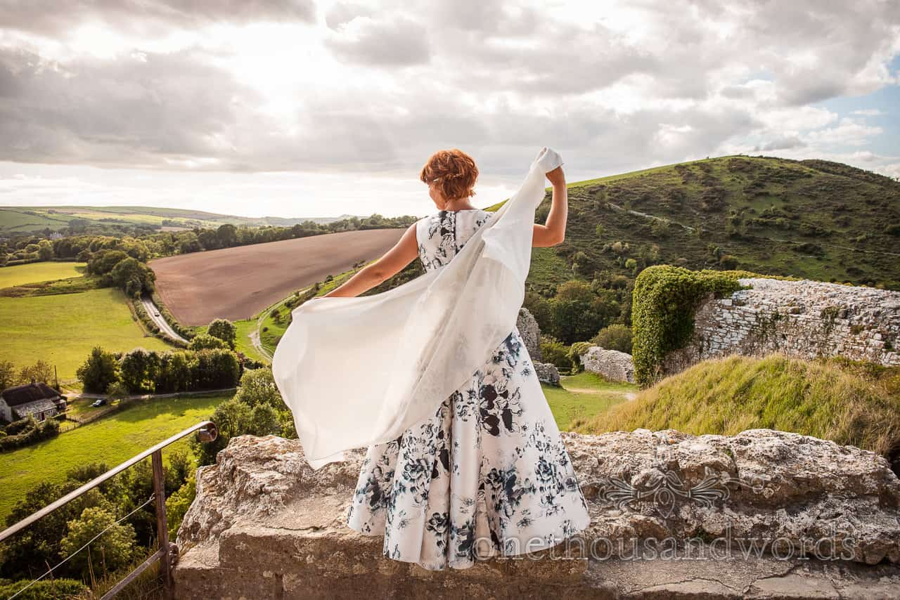 Bride in floral print wedding dress with Dorest countryside from Corfe Castle wedding photographs