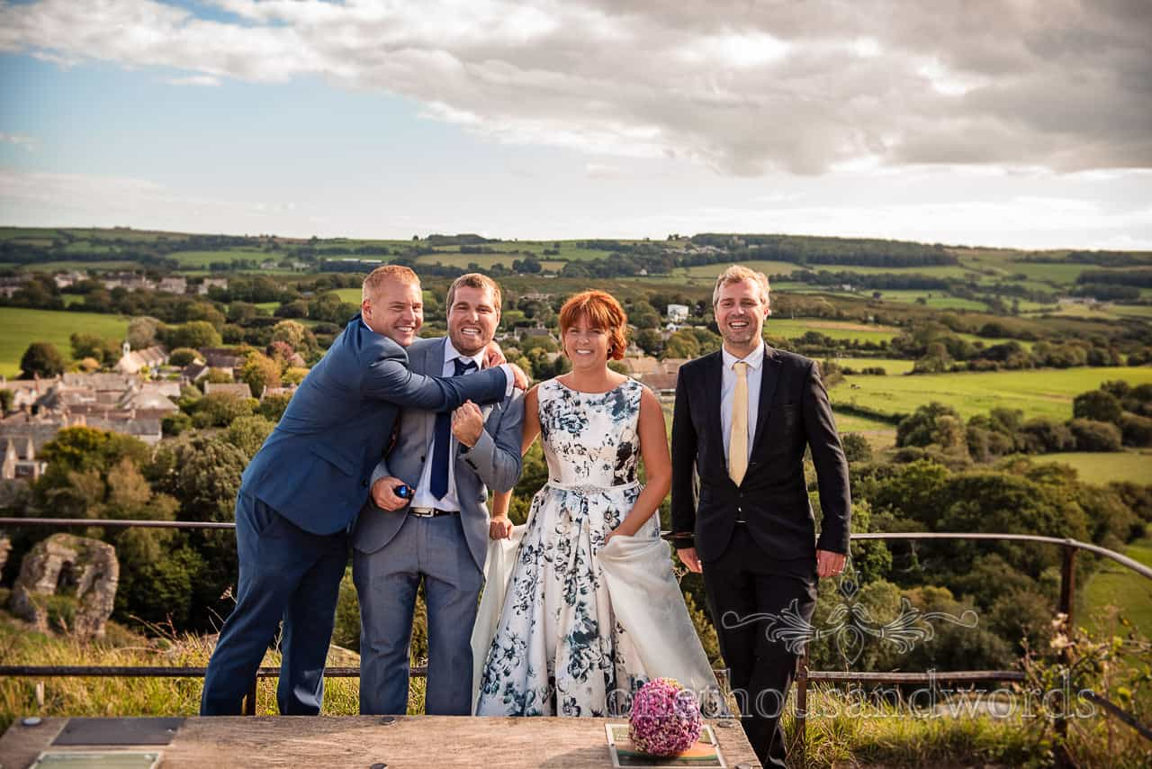 Wedding party funny group photograph with countryside view from Corfe Castle