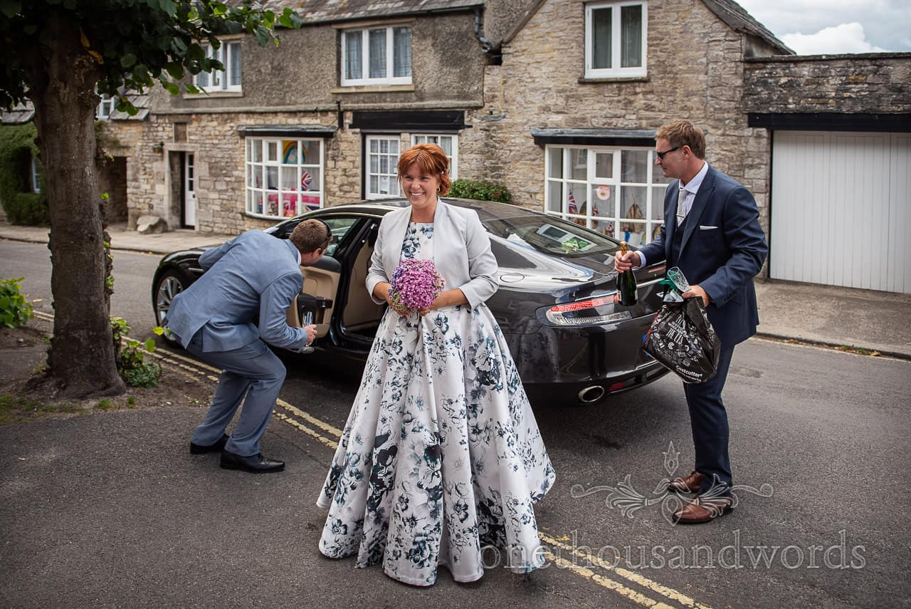 Bride and groom arrive as best man check out Aston Martin wedding car