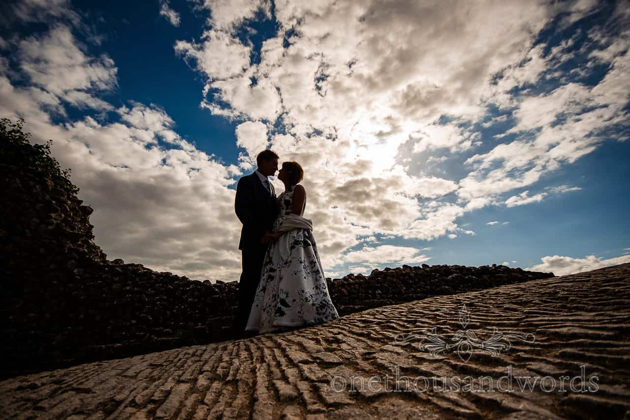 Corfe Castle wedding photographs of bride and groom silhouette against cloudy blue sky