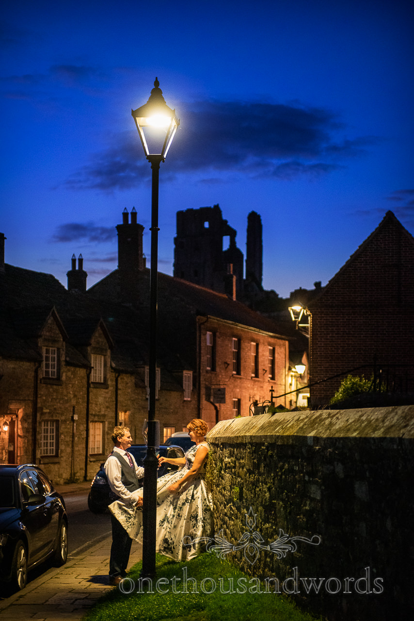 Bride and groom couple photograph under lamppost in Corfe Castle Dorset stone village at night