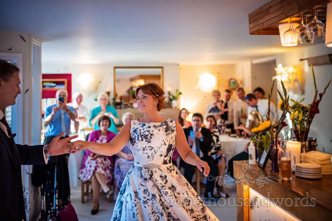 Elegant bride in floral print wedding dress twirls during first dance
