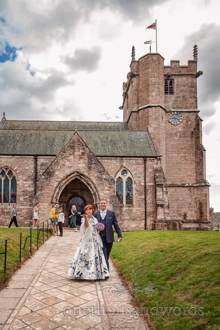 Bride and groom blow kisses outside St Edwards church wedding venue in Corfe