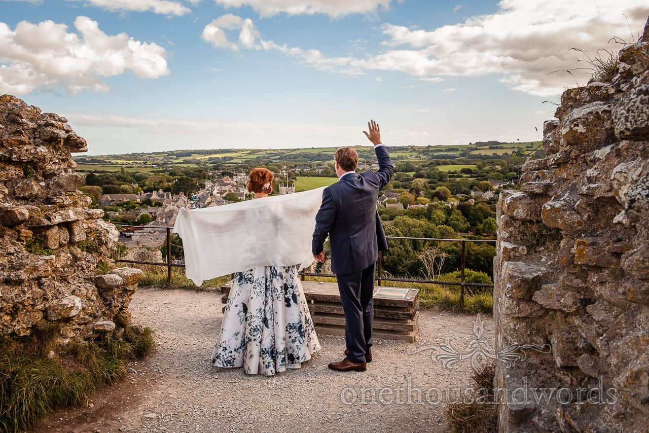 Bride and groom wave to wedding guests from the top of Corfe Castle in Dorset