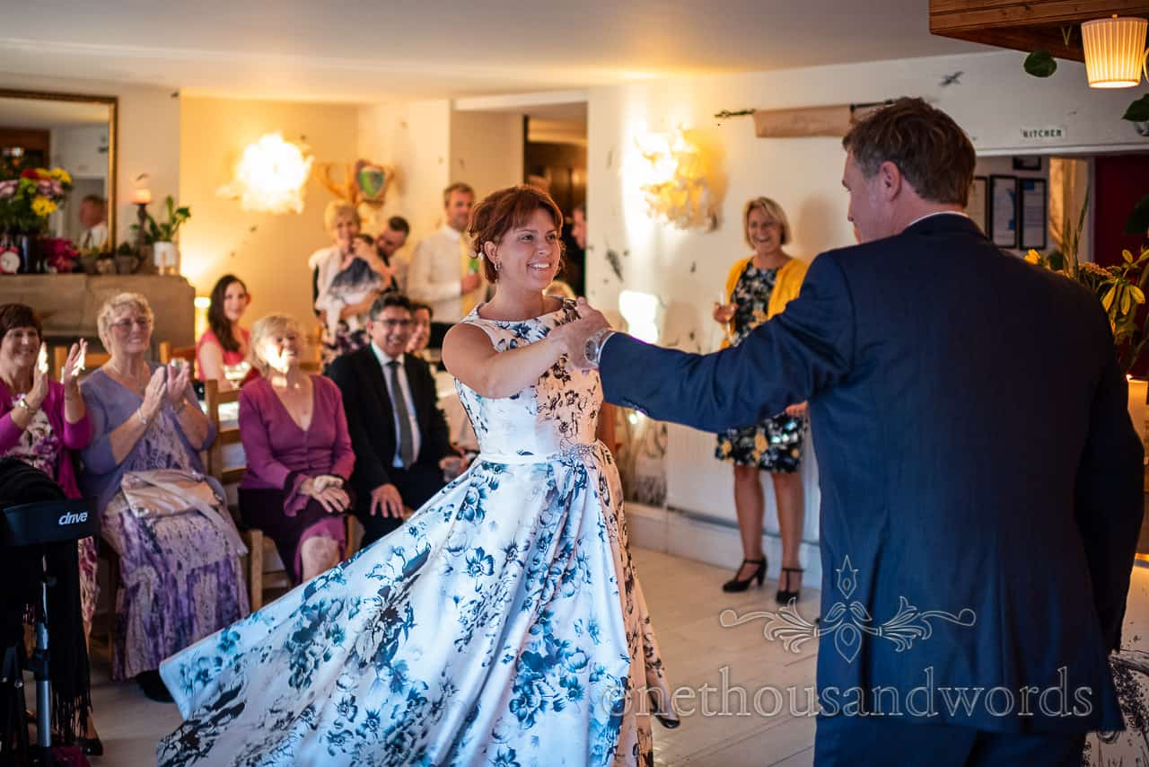 Bride twirls whilst jazz dancing with groom and clapping wedding guests