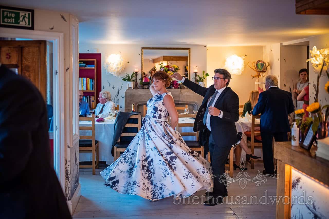 Bride in floral print dress is twirled around Dorset restaurant venue dancefloor by guest