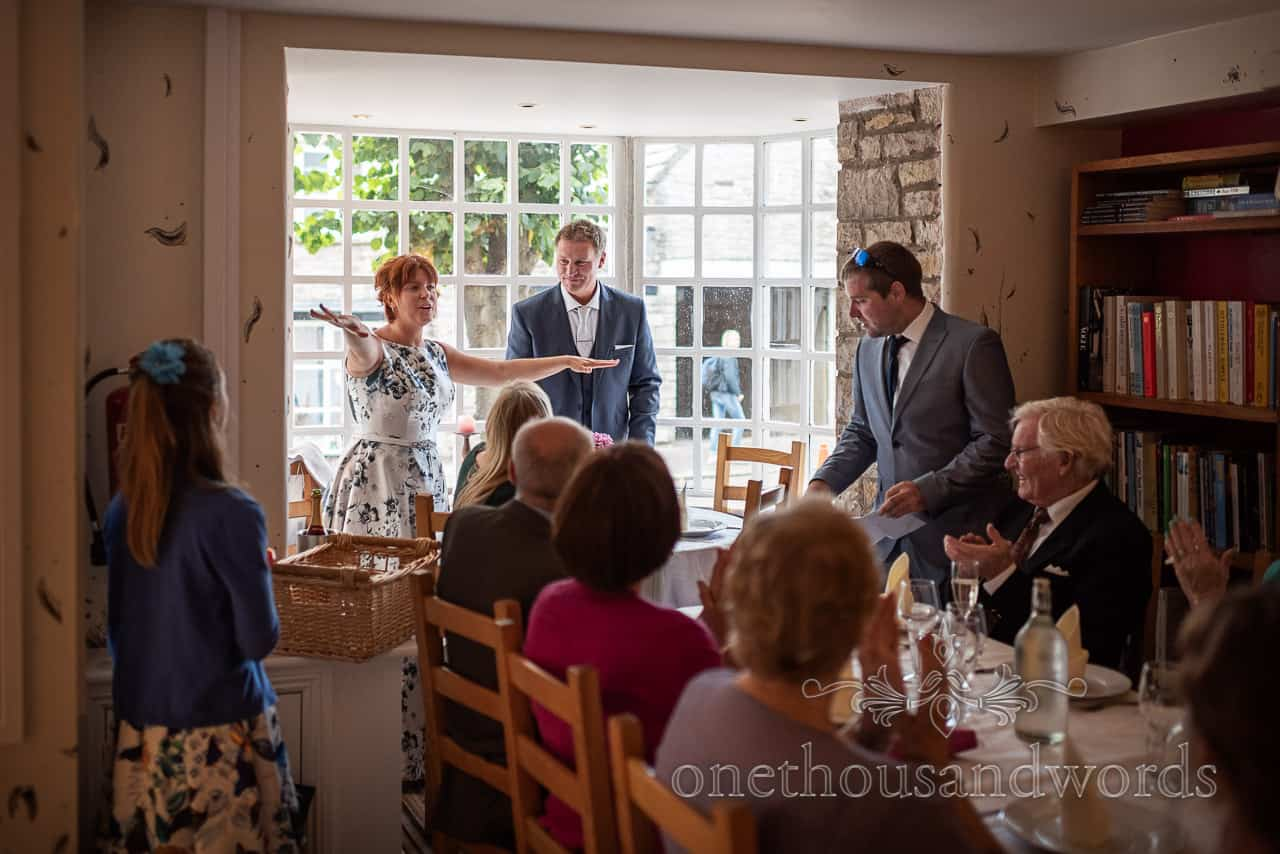 Bride makes wedding speech with arms out wide in Dorset restaurant