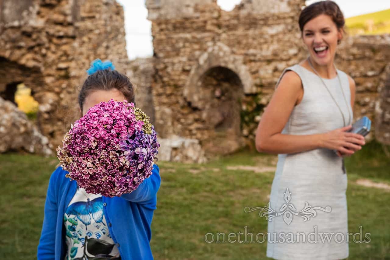 Child wedding guest holds bridal flower bouquet over her face as other wedding guest laugh in Dorset castle ruins