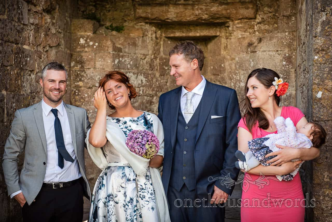 Wedding group laughing before photographs in Corfe Castle, Dorset