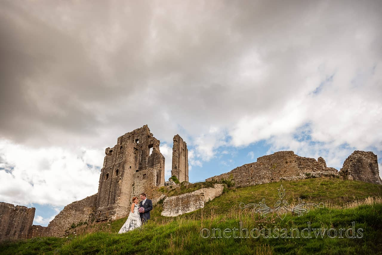 Corfe Castle wedding photographs with bride and groom under dramatic clouds