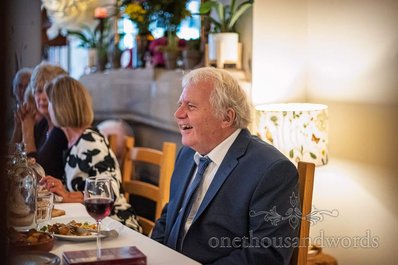 father of the groom laughing during Dorset restaurant wedding breakfast meal