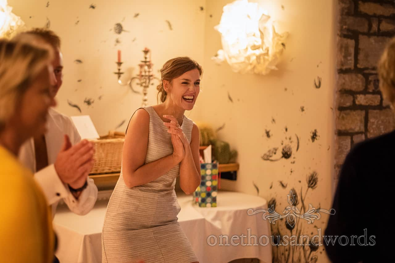 laughing female wedding guest claps at wedding evening dancing