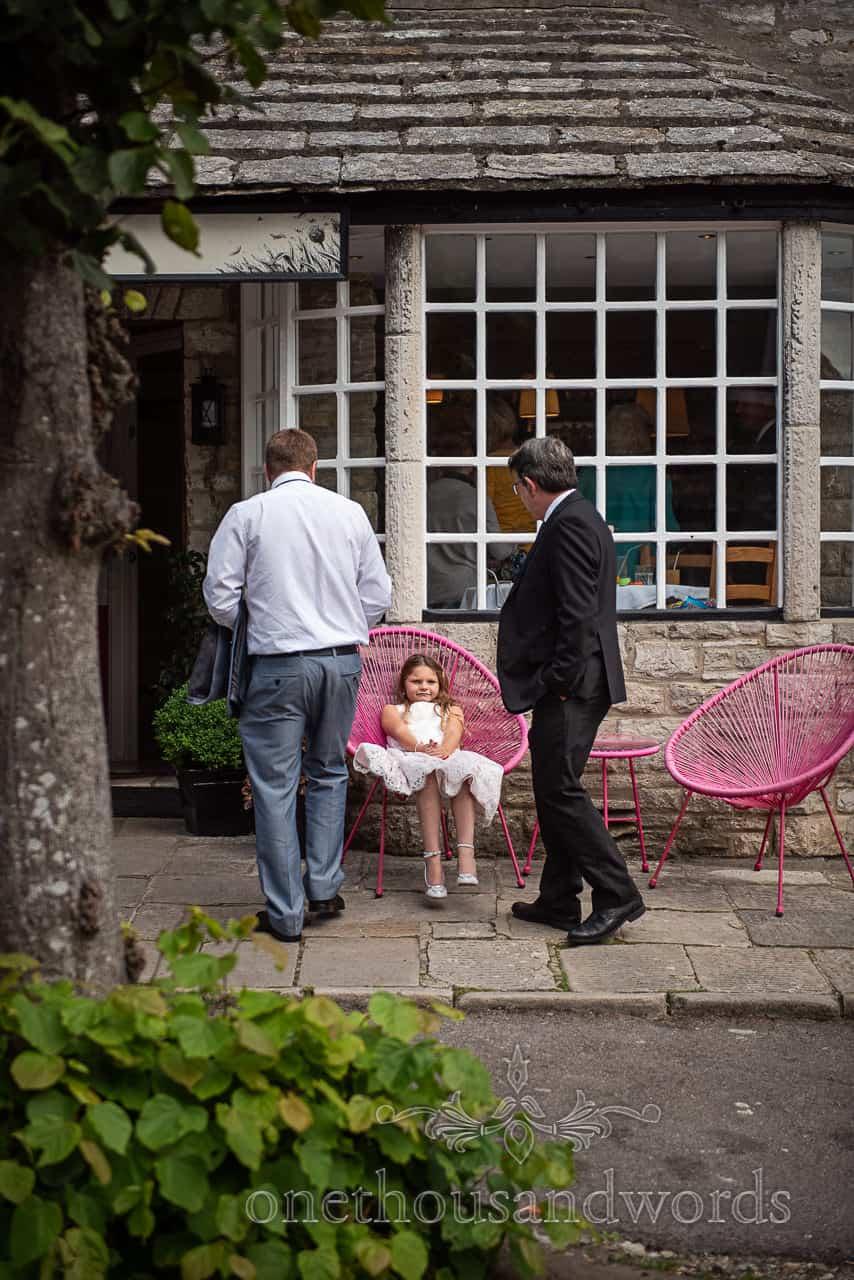 Flower girl sits in designer pink chair outside Dorset restaurant wedding venue