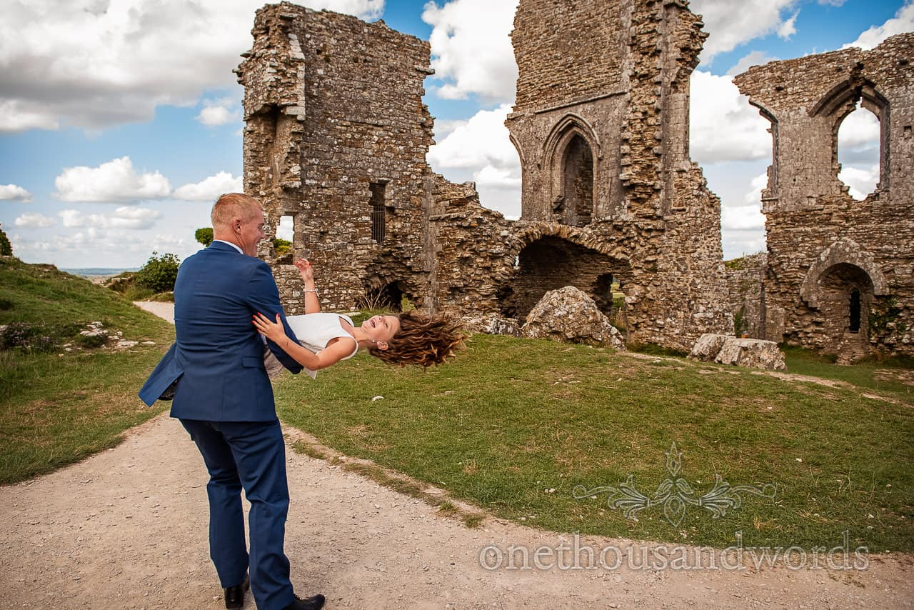 Flower girl is spun around by her father in castle ruins