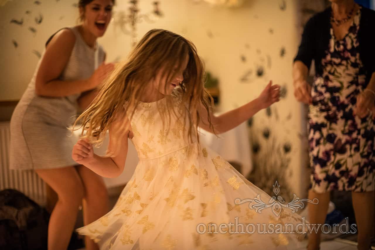 Flower girl in golden butterfly dress twirls on wedding dancefloor