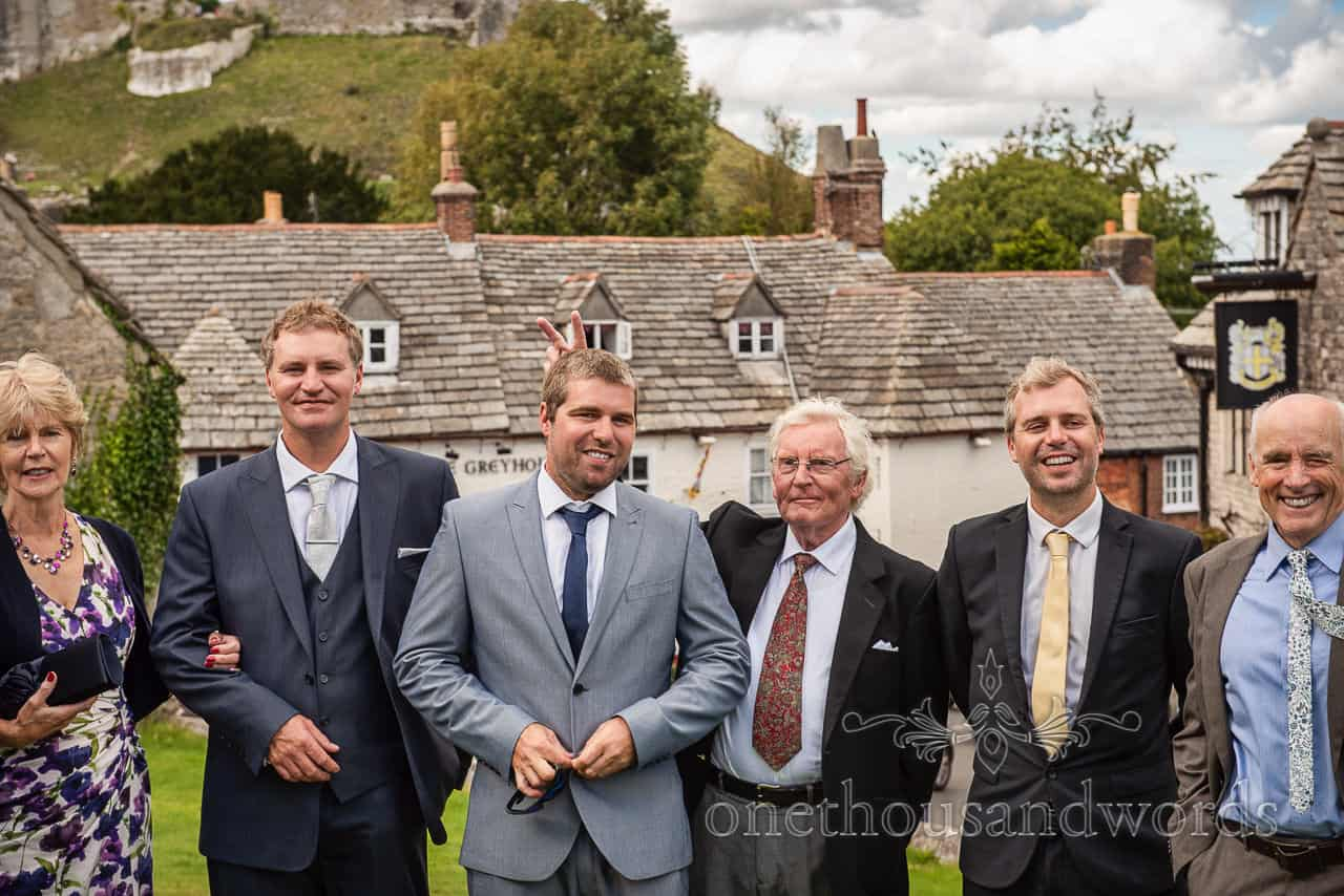 Funny wedding group photograph with Corfe Castle in the background